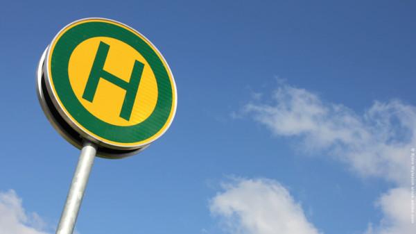 gelb-grünes Haltestellenschild vor blauem Himmel
