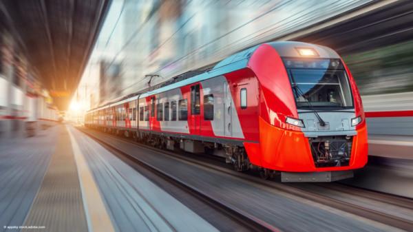 Zug fährt durch einen Bahnhof